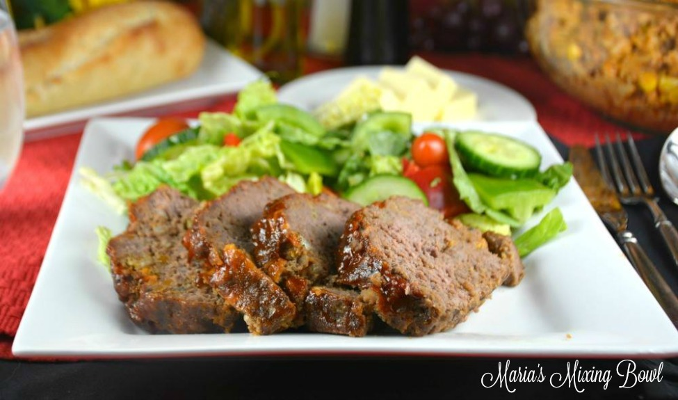 Meatloaf on white plate with salad mashed potatoes and bread in background