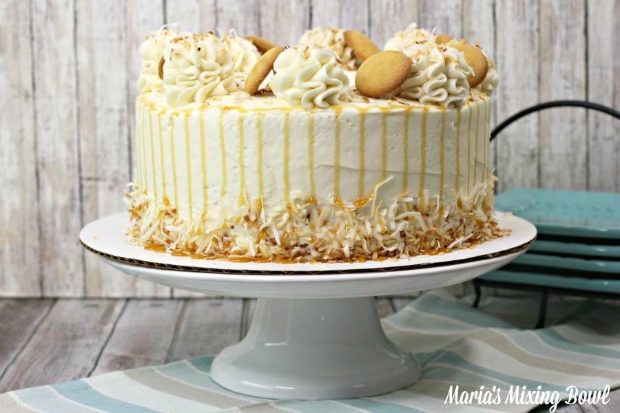 Whole banana pudding cake on white cake tray.