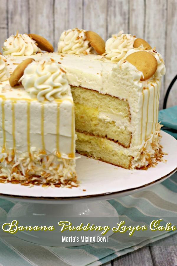 Banana pudding layer cake with slice missing on white cake tray
