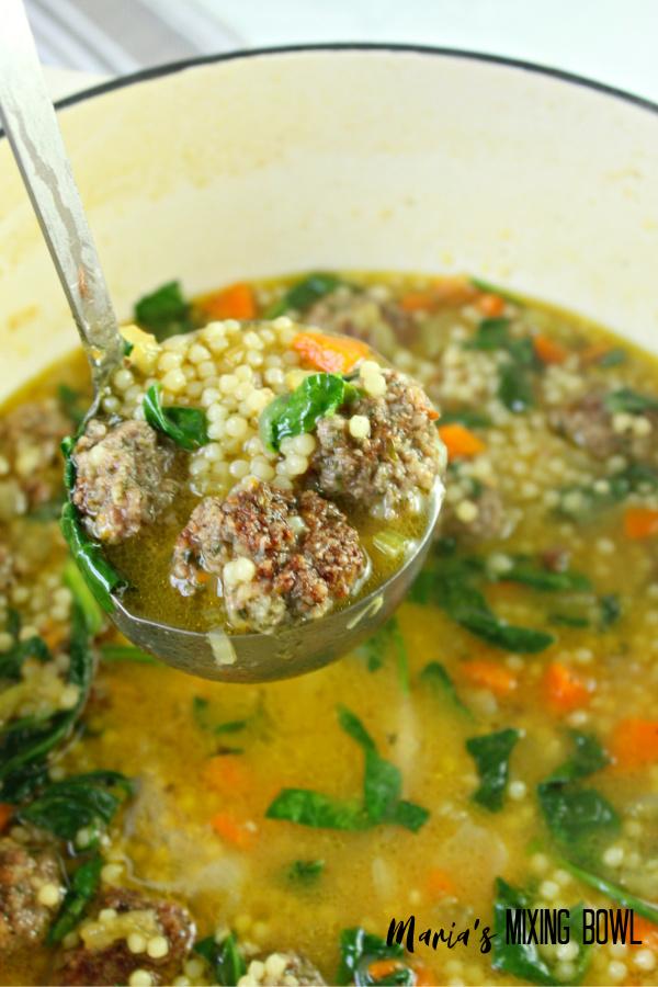 a ladle of wedding soup in a soup pot