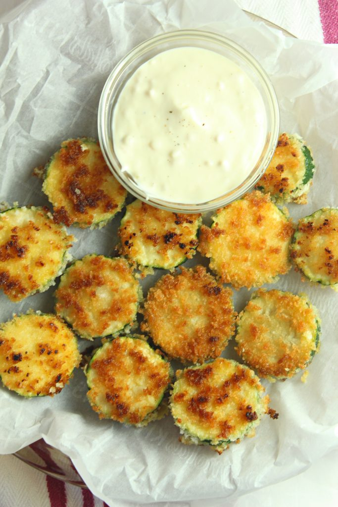 cooked zucchini rounds on white paper with sauce