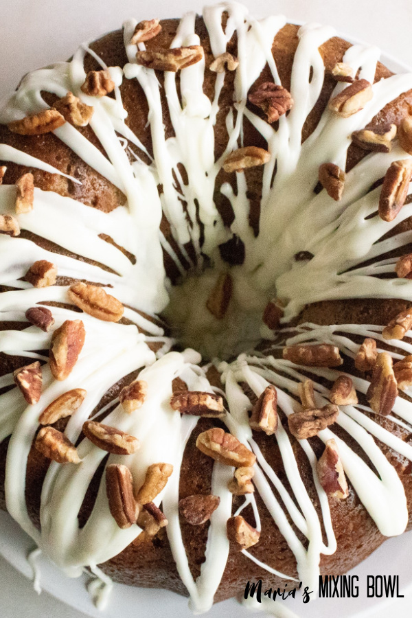 cake with frosting and pecans on a white plate