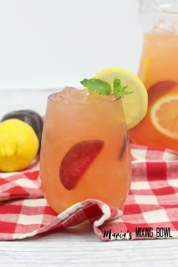 Citrus Plum Whiskey Smash with fruit and pitcher