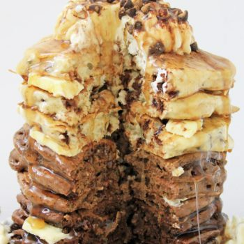 A stack of ombre pancakes with chocolate chips topped with butter and chocolate chips with chok of ombre chocolate