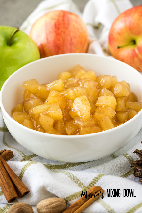 chopped canned apples in a white bowl with fresh apples on a white and brown striped towel