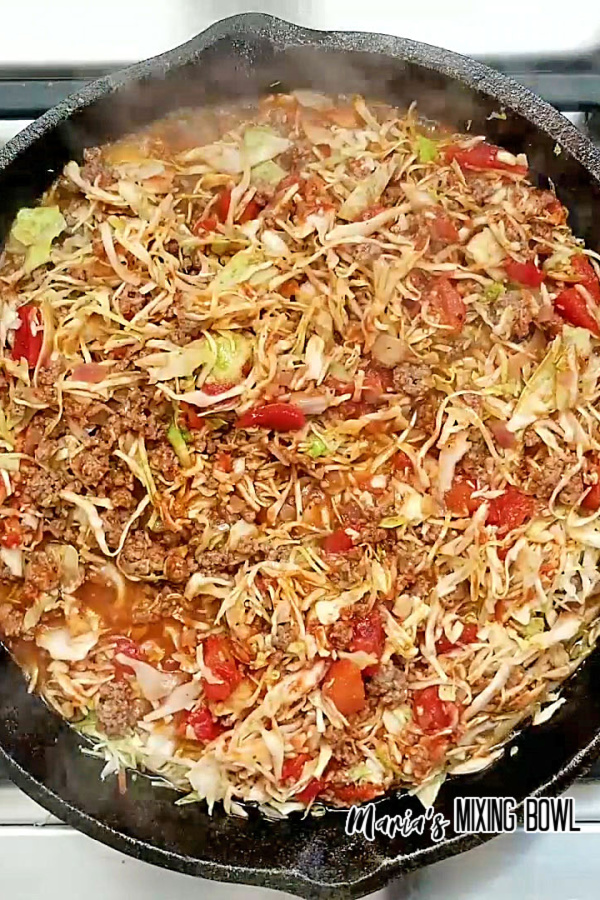 cabbage cooking in an iron skillet