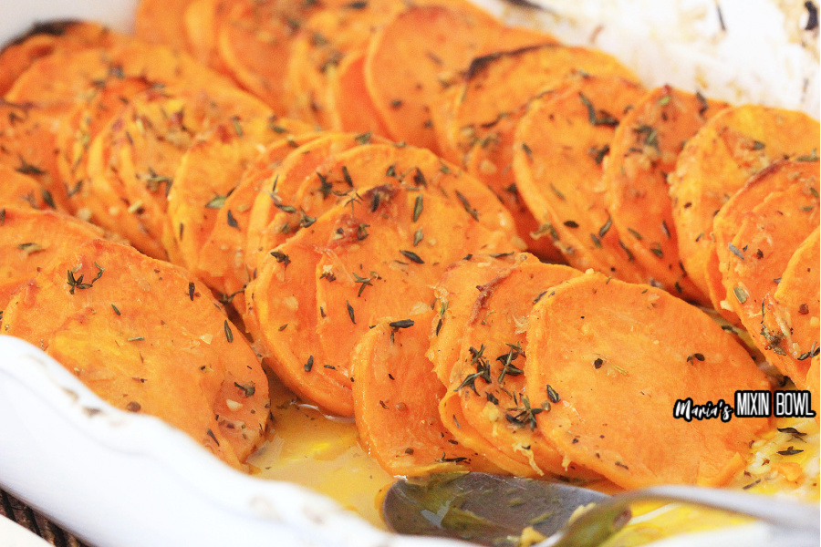 sliced and cooked sweet potatoes in a white baking dish ready to serve