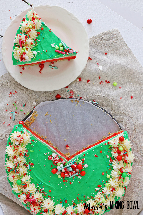 no bake Christmas cheesecake on white plate and cake on the bottom on a beige napkin