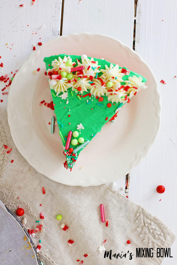 slice of Christmas cheesecake dessert with sprinkles on a white plate