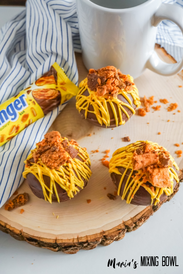 3 hot chocolate butterfinger bombs on a wood board with a white and blue napkin and white cup and candy bar