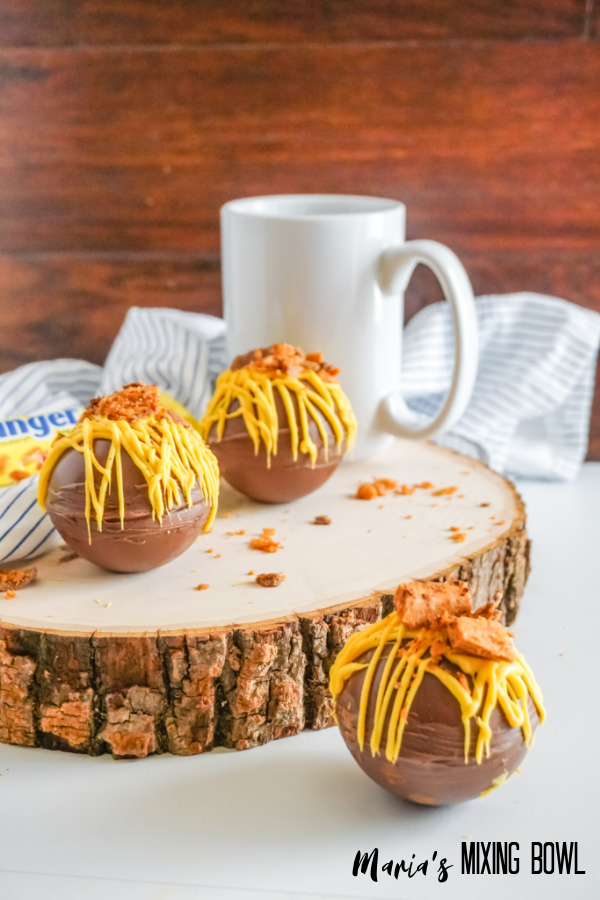 hot cocoa bombs wih yellow candy melt on a wooden board, white cup and white and blue strip napkin