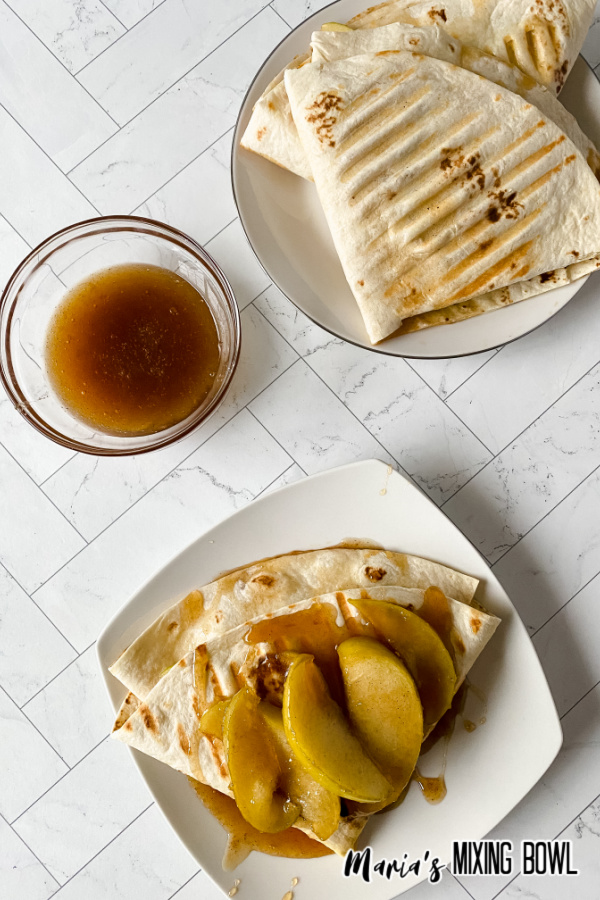 Two white plates with caramel apple wraps.