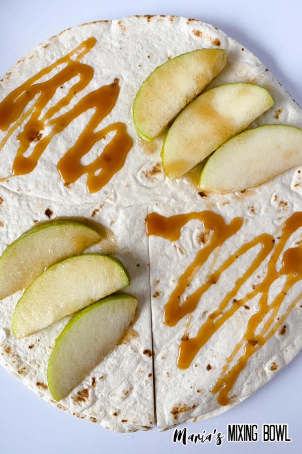 Caramel and apple slices on tortilla before cooking.