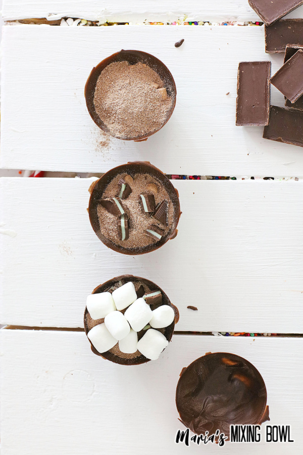 Four cocoa bomb halves showing filling process on white table