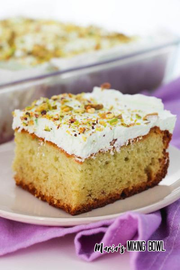 Slice of cake on white plate with baking dish full of more cake in background.