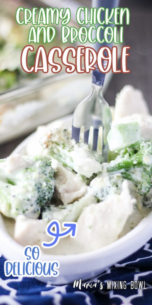 Fork stuck into creamy chicken and broccoli casserole in white dish