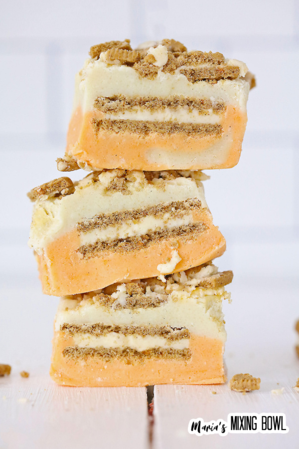 Closeup shot of three pieces of carrot cake fudge stacked atop one another.