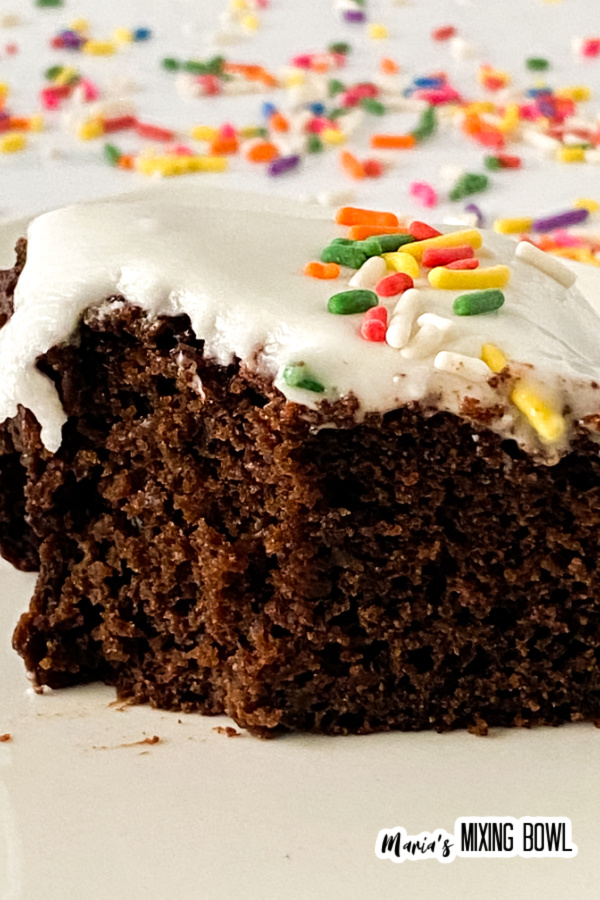 Slice of cake with white frosting and sprinkles