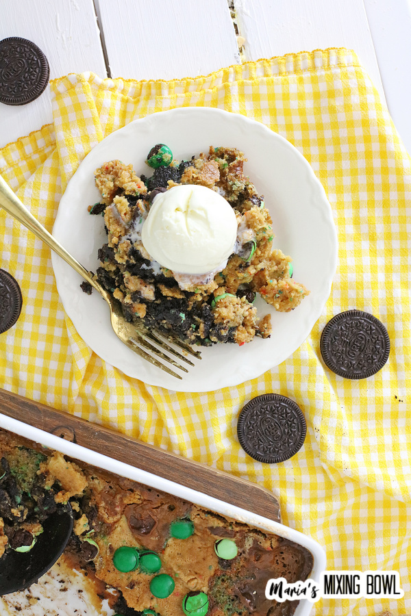 Overhead shot of dump cake topped with ice cream on white plate