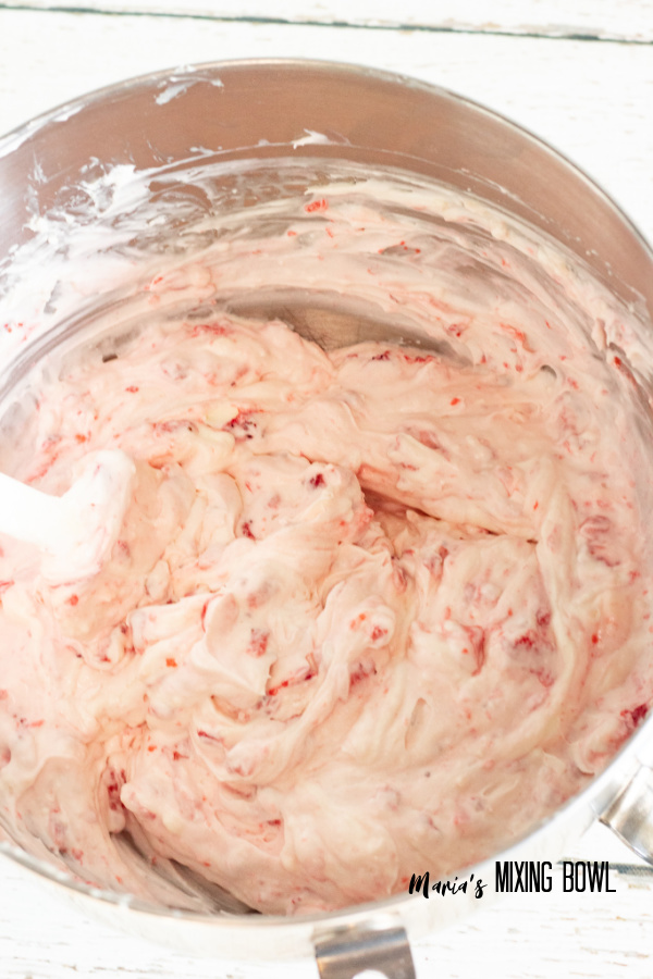 Cream filling with strawberries mixed in in mixing bowl