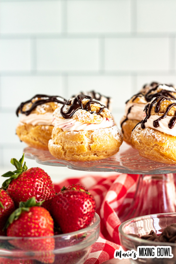 Cream puffs on glass cake dish with bowl of strawberries and bowl of chocolate chips in front