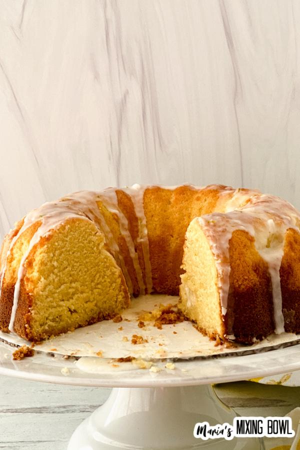 Glazed lemon lime bundt cake with a few slices removed on cake stand