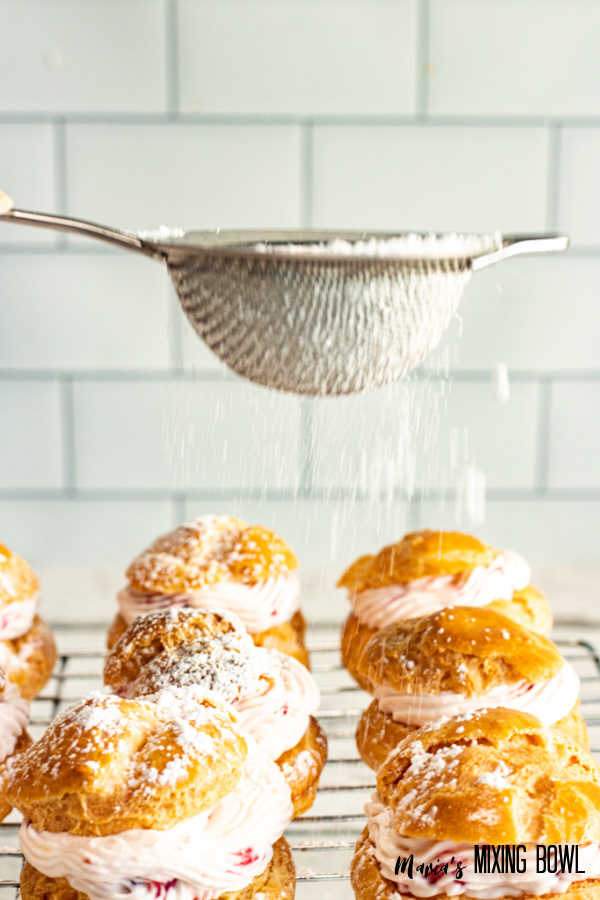 Sifter being used to sprinkle powdered sugar over strawberry cream puffs on wire rack