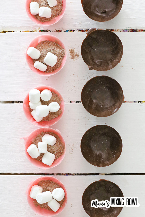 Overhead shot of cocoa bombs filled with ingredients and ready to be filled