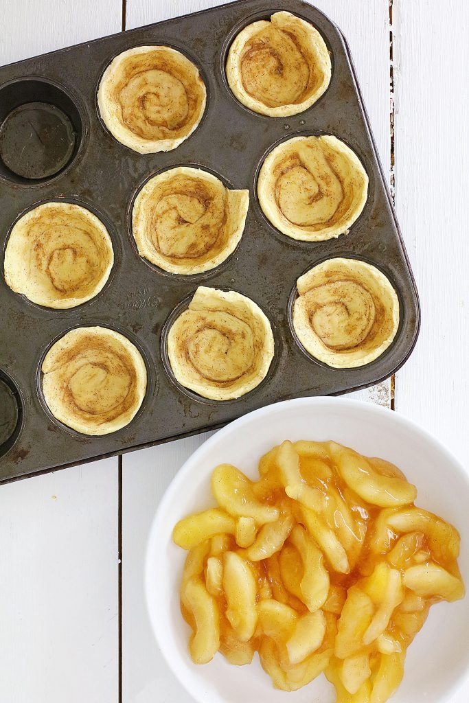 cinnamon rolls and apples in a white bowl