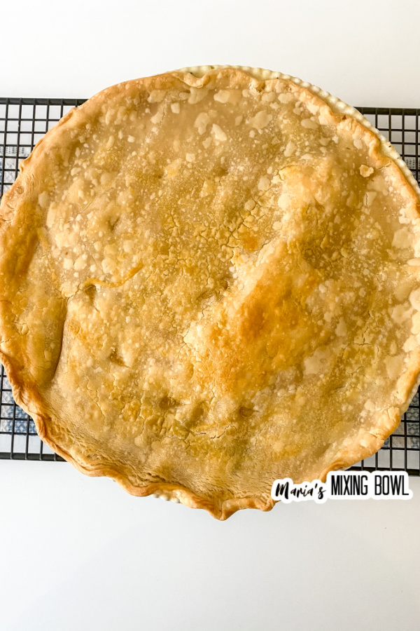 Overhead shot of cooked whole rustic chicken pot pie on wire rack