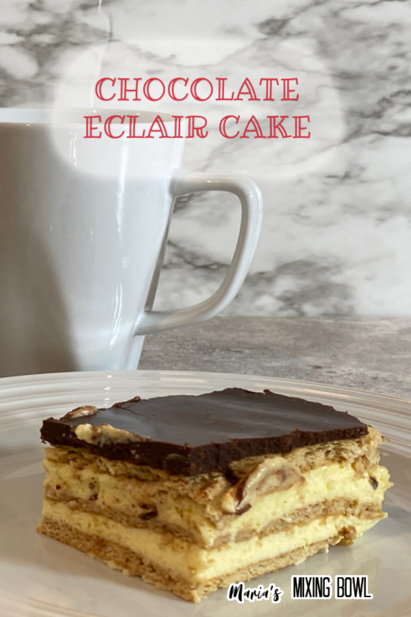 Closeup shot of slice of chocolate eclair cake on white palte with coffee mug in background