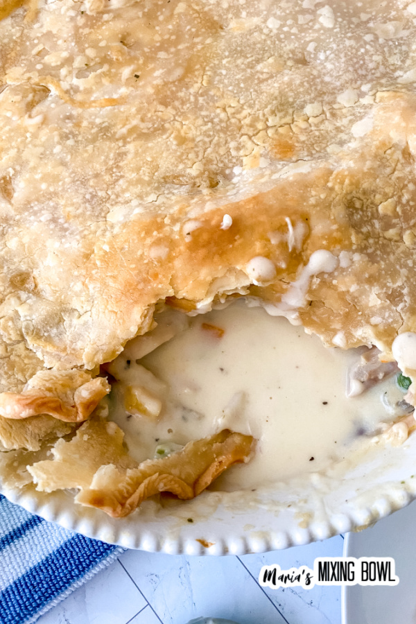 Overhead closeup shot of rustic chicken pot pie with scoop removed in pie plate