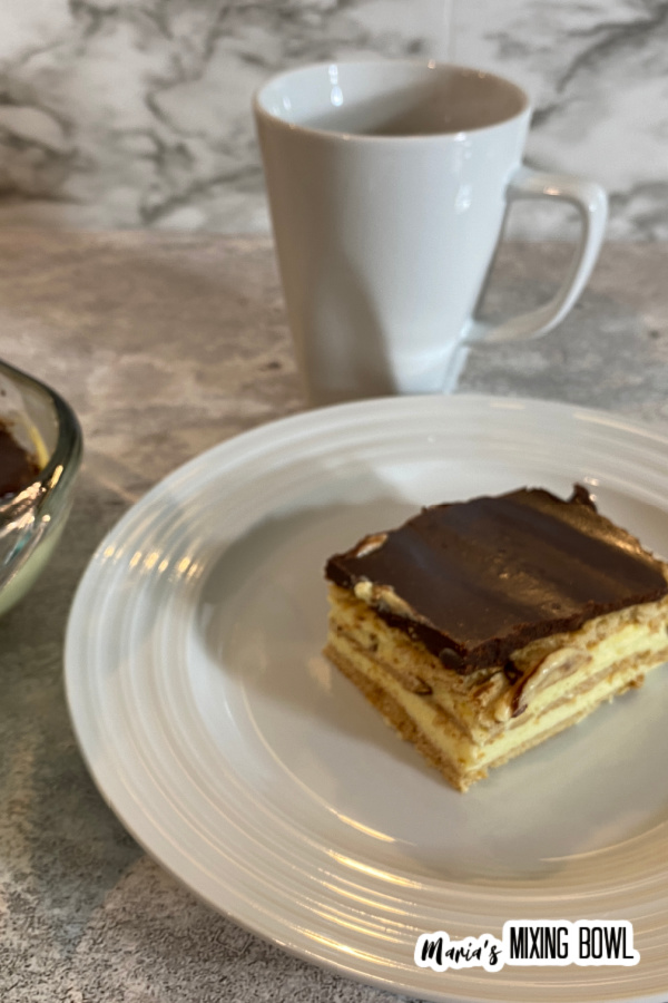 Slice of chocolate eclair cake on white plate with coffee mug in background