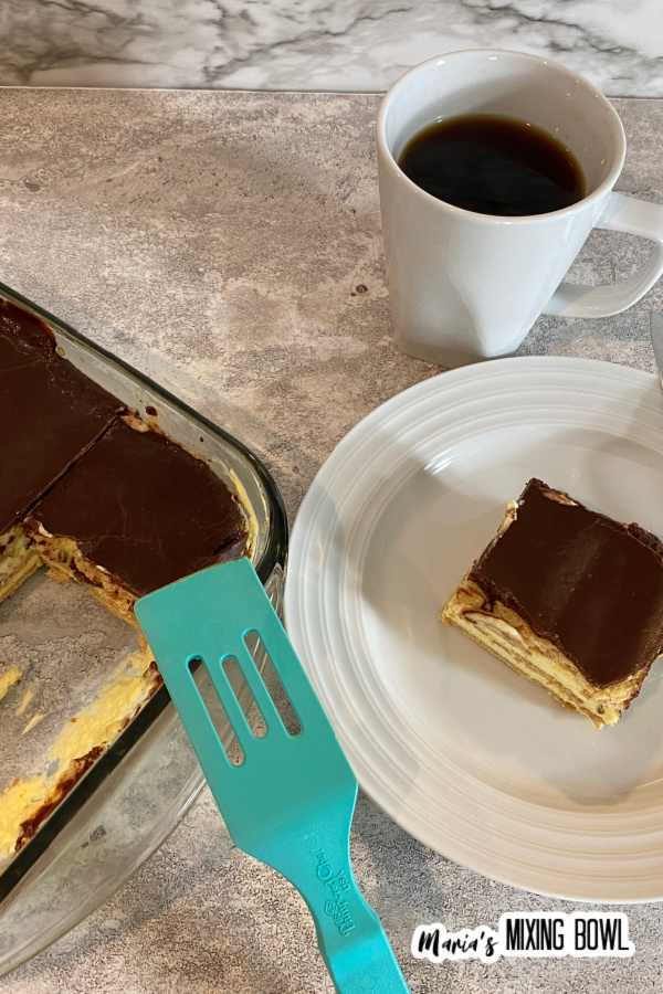 Overhead shot of chocolate eclair cake in glass baking dish next to piece of cake on white plate