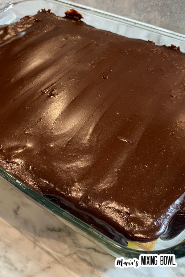 Whole chocolate eclair cake in glass baking dish.