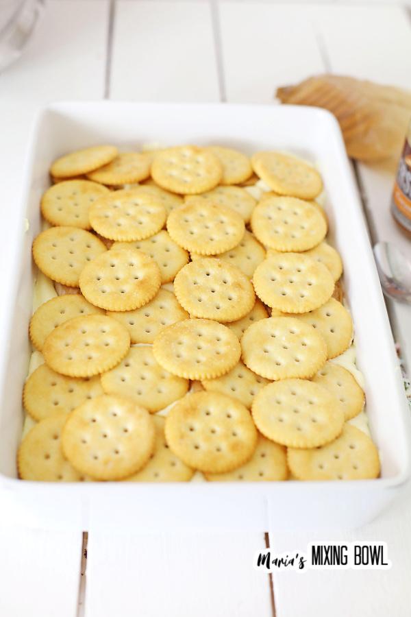 Ritz crackers lining bottom of white baking dish