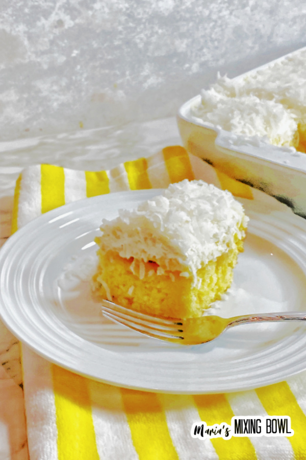 Slice of pineapple coconut poke cake with fork on white plate with more poke cake in baking dish in background