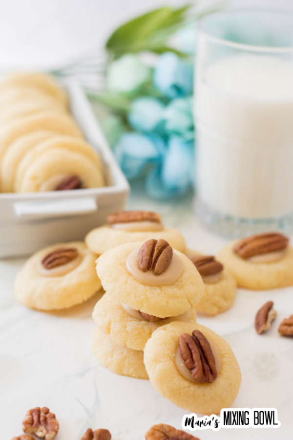 Caramel pecan thumbprint cookies in a white tray and white table