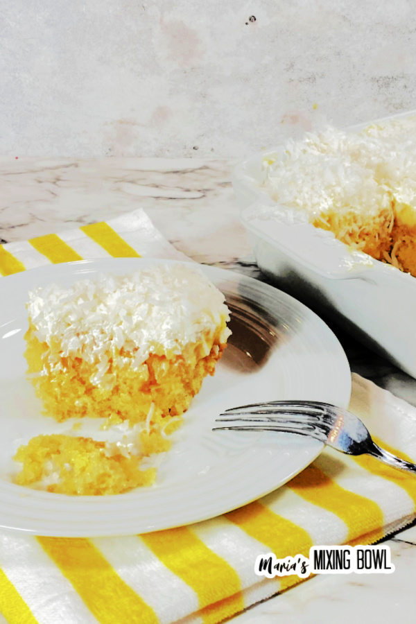 Closeup shot of slice of pineapple coconut poke cake with fork on white plate