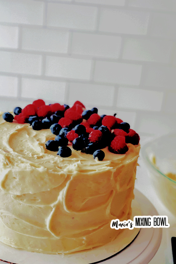 Medium shot of whole berry chantilly cake on cake stand