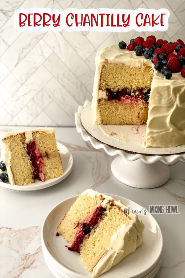 Two slices of berry chantilly cake on plates with the rest of cake on cakestand