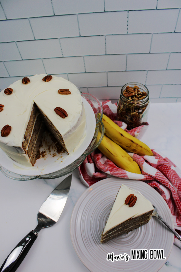 Overhead shot of cake slice on plate next to the rest of the cake on a cake stand
