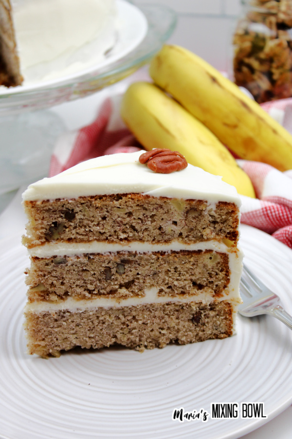 Slice of hummingbird cake on white plate with bananas in background