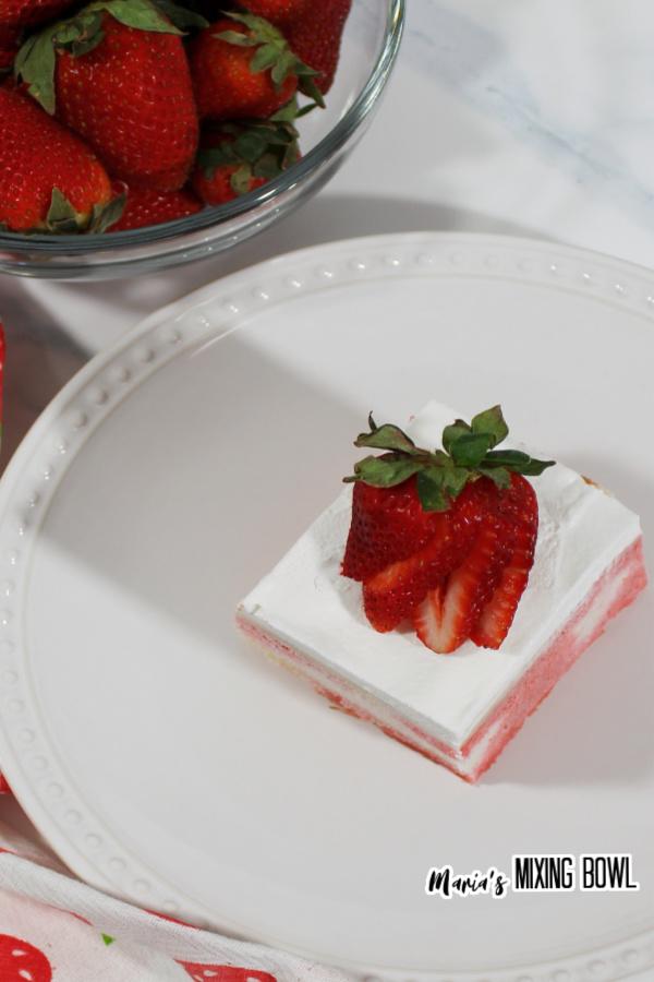 Overhead shot of strawberry cheesecake poke cake on white plate