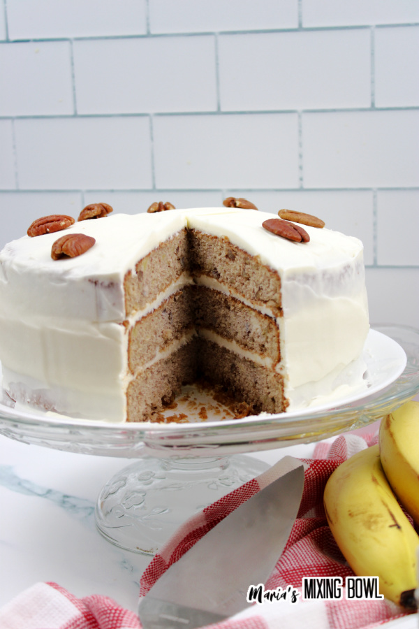 Old fashioned hummingbird cake with slice removed on cake stand.