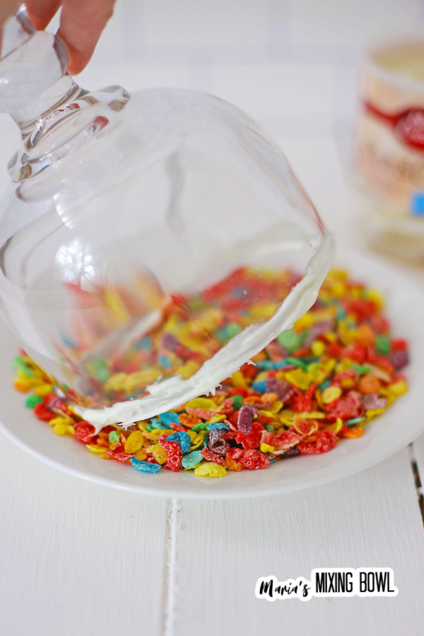 Glass with fosting on rim being dipped in Fruity Pebbles