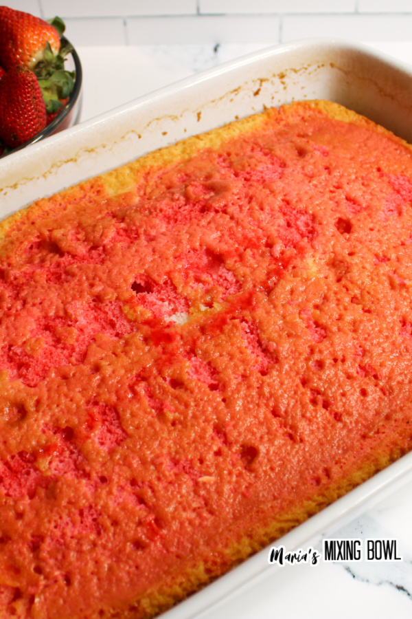 Cake in baking dish with holes poked in it and soaked in strawberry Jello