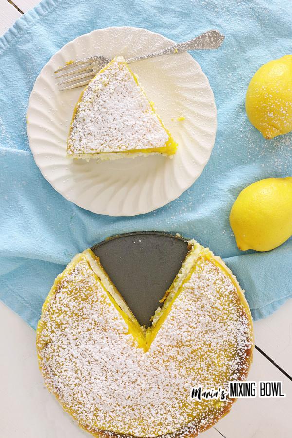 Overhead shot of slice of lemon bar cheesecake on white plate next to whole lemon bar cake