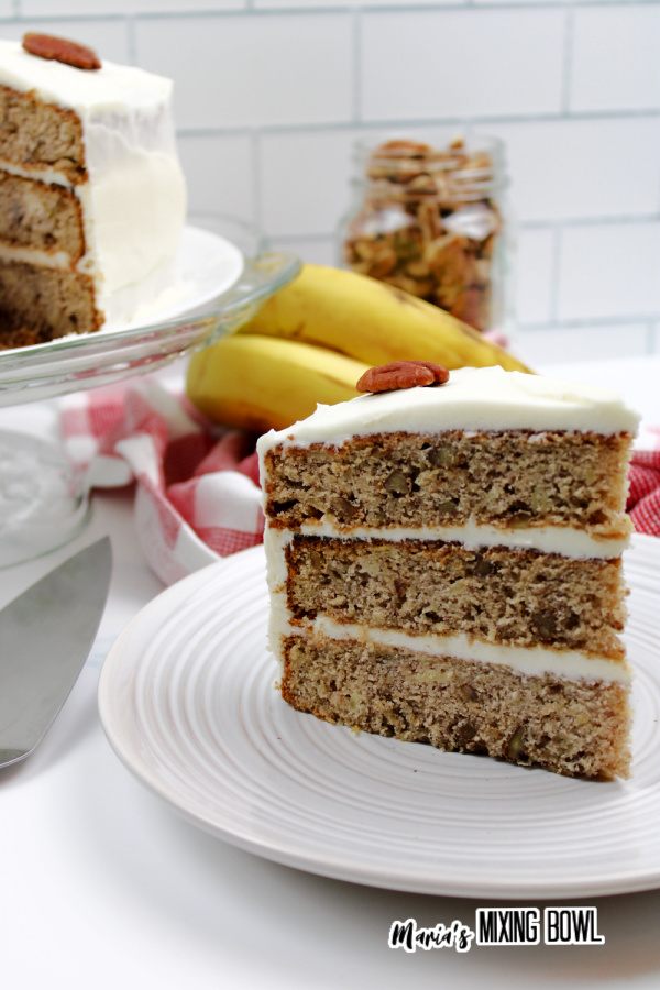 Slice of hummingbird cake on plate with more cake on cake stand in background