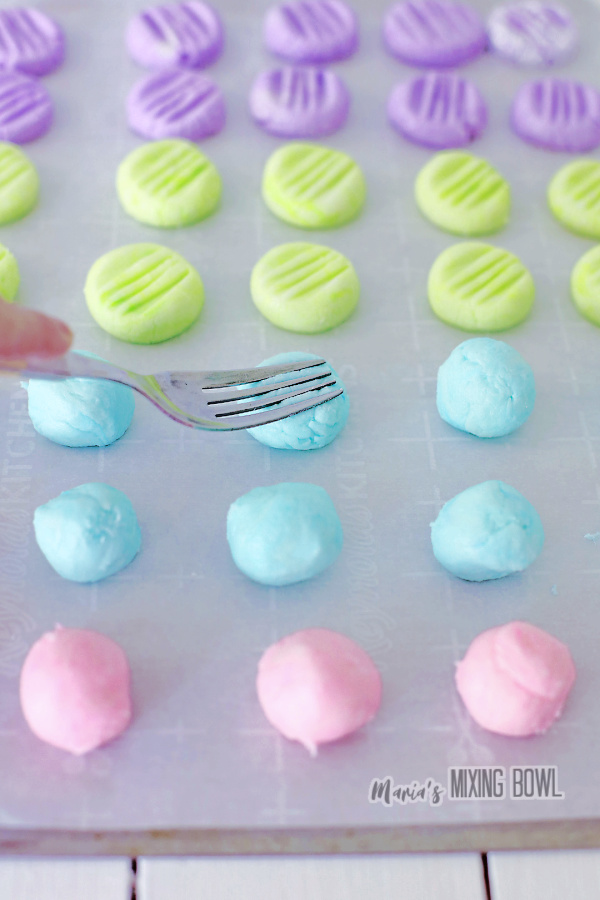 Fork pressing down cream cheese mints on parchment paper-lined baking sheet